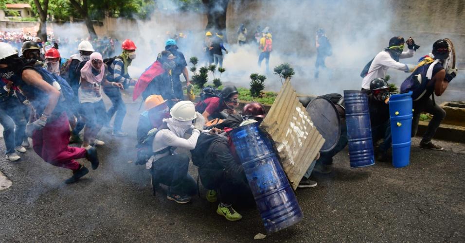 ATOS ANTI-MADURO - Opositores venezuelanos protegem-se em barricada durante confrontos com a polícia durante manifestação contra o presidente Nicolás Maduro em Caracas