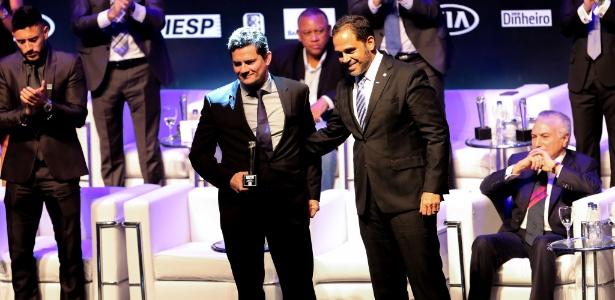 """Presidente Michel Temer (d) fica sentado enquanto juiz Sérgio Moro recebe prêmio de brasileiro do ano em evento da revista """"IstoÉ"""", em São Paulo"""