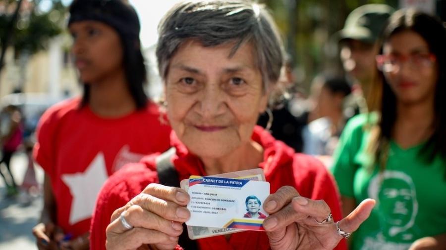 """Venezuelana mostra seu """"Carnet de la patria"""" - AFP"""