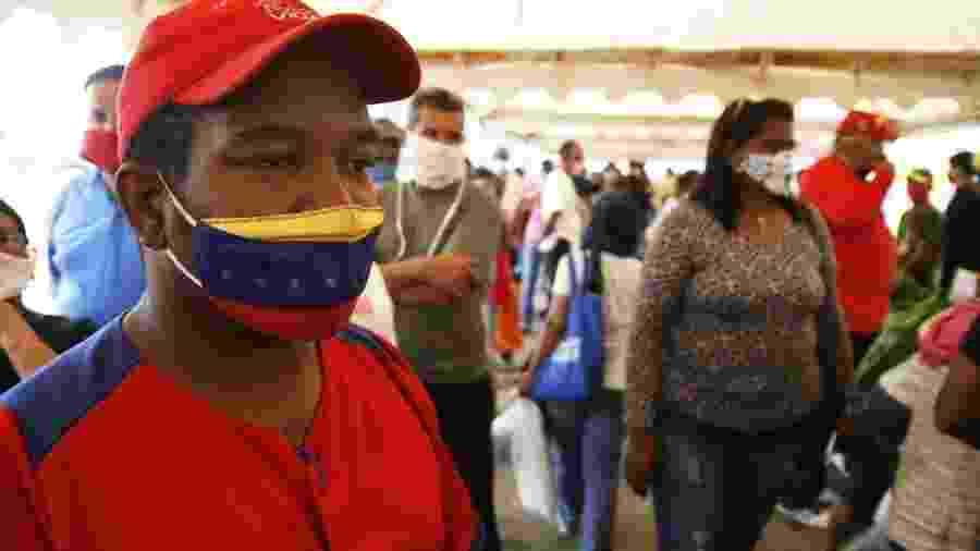 2.mai.2020 - De máscara, homem aguarda para receber cesta básica fornecida pelo governo da Venezuela durante a pandemia - Humberto Matheus/NurPhoto via Getty Images
