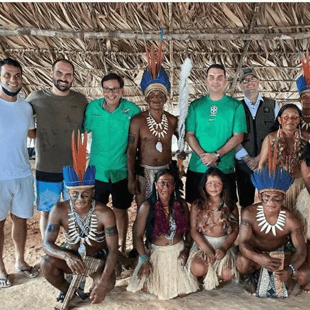 Flávio e Eduardo Bolsonaro posam sem máscaras ao lado de indígenas - Divulgação/Gilson Machado