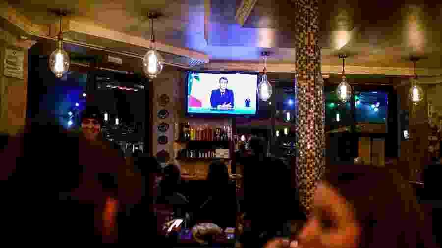 28.out.2020 - Clientes de um café em Paris assistem ao pronunciamento do presidente Emmanuel Macron, que anunciou lockdown de um mês por causa da covid-19  - Martin Bureau/AFP