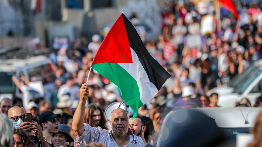 Manifestante com bandeira da Palestina durante protesto contra ocupação israelense em Jerusalém - Ahmad Gharabli/AFP
