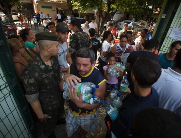 Moradores de Governador Valadares (MG) fazem fila para pegar garrafas de água mineral distribuídas pelo Exército, nesta sexta-feira (13) - Lincon Zarbietti/O Tempo/ Estadão Conteúdo