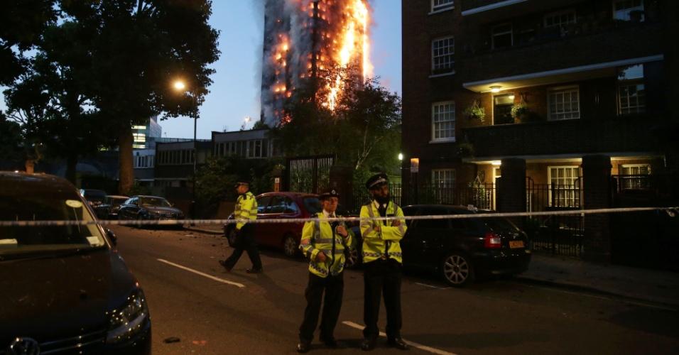 14.jun.2017 - Policiais fazem segurança do perímetro onde está localizado o prédio atingido por chamas em Londres