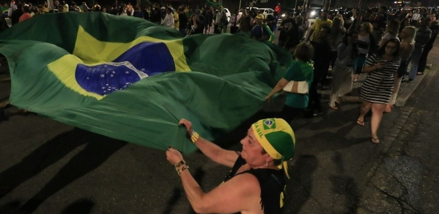 Manifestantes empunham bandeira do Brasil em frente à sede da PF em Curitiba