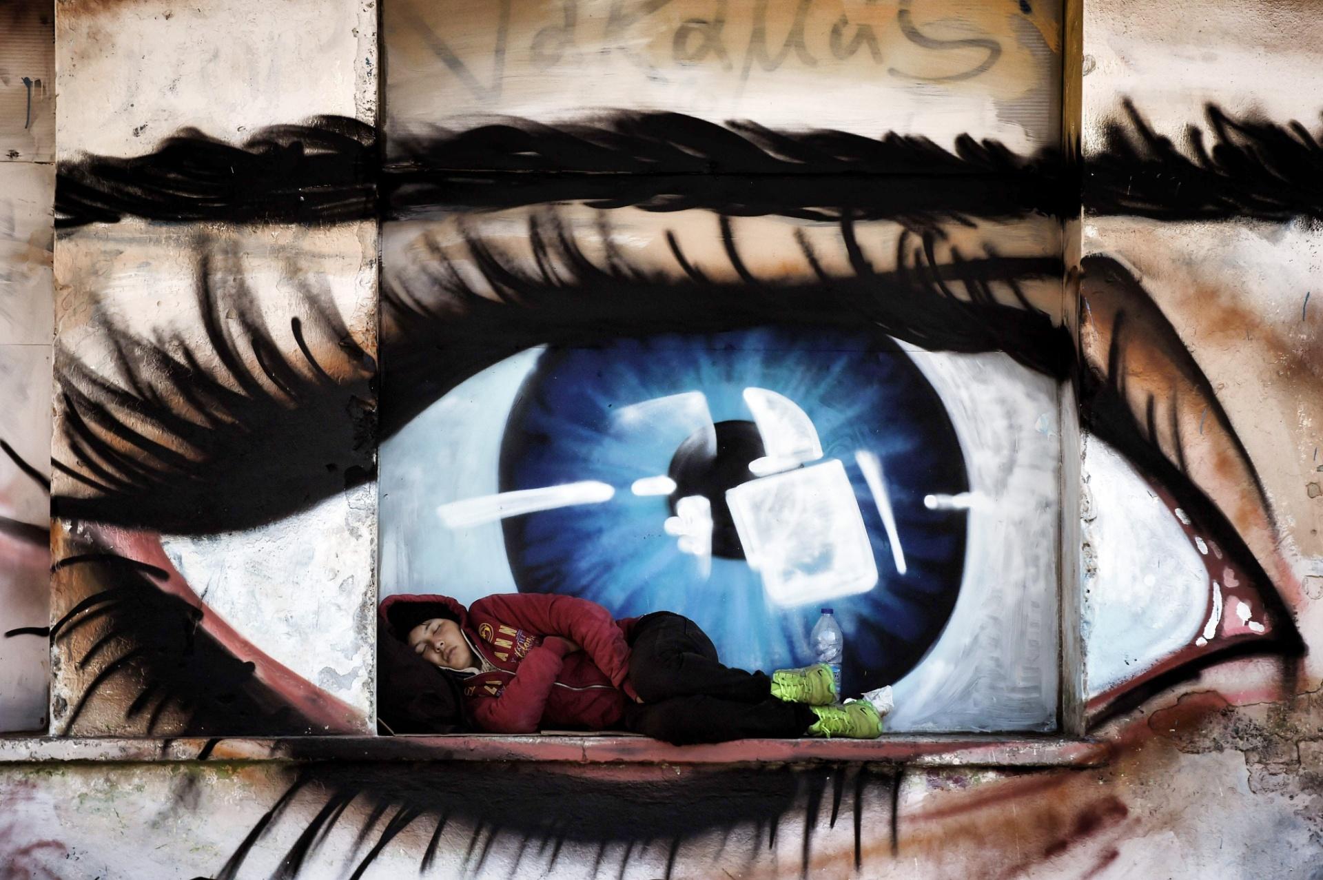 06.out.2015 - Mulher refugiada dorme em janela pintada com o grafiti de um olho, no porto de Mytilene, na ilha de Lesbos, Grécia