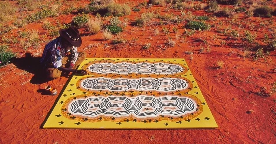 26.nov.2015 - Um artista aborígene pinta no deserto australiano. As artes visuais são há muito tempo uma forma dos povos indígenas contarem suas histórias