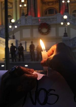 Manifestante acende vela em frente ao Palácio da Guanabara, no Rio de Janeiro, durante ato contra as mortes de cinco rapazes, em Costa Barros