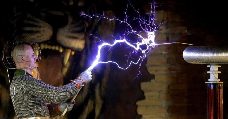 15.fev.2016 - Os raios da bobina de Tesla são produzidos a partir da variação de tensão entre duas bobinas. As bobinas são formadas por muitos fios enrolados. Visitante interage com raios elétricos