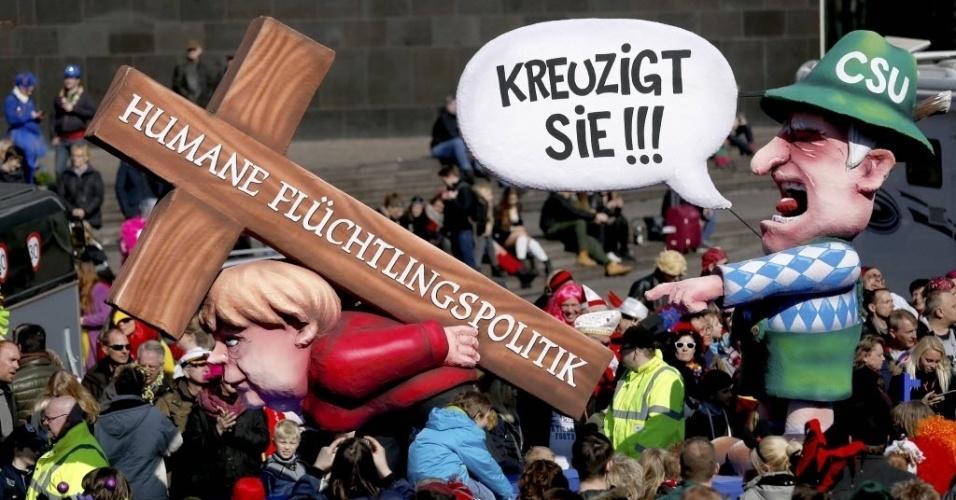 """13.mar.2016 - Um carro alegórico com caricatura do governador da Bavária, Horst Seehofer, e da chanceler alemã, Angêla Merkel, desfila em carnaval fora de época em Duesseldorf, na Alemanha. O desfile original, que seria realizado em fevereiro, foi cancelado devido ao mal tempo. Nas figuras, Seehofer diz """"crucifique ela"""", enquanto Merkel carrega cruz com os dizeres """"direitos humanos para imigrantes"""""""