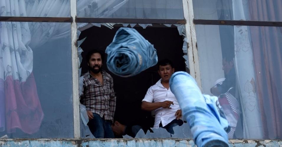 4.ago.2016 - Comerciantes afegãos atiram rolos de tecido de um shopping em Cabul. Um incêndio de grandes proporções provocou perdas aos lojistas. A causa do fogo ainda não foi determinada