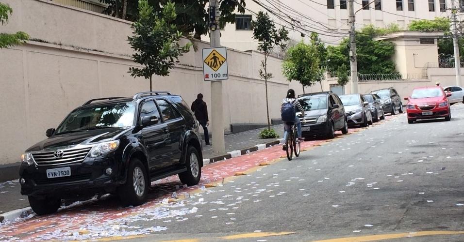 2.out.2016 - Em rua tomada de santinhos, carros param sobre a ciclovia em votação no Colégio Maria Cabrini, na Vila Mariana, em São Paulo