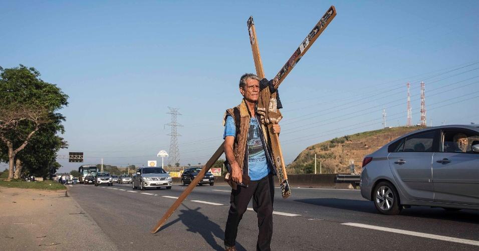 12.out.2017 - O romeiro Nelson Batista caminha pela via Dutra em direção à Basílica de Nossa Senhora Aparecida carregando uma cruz
