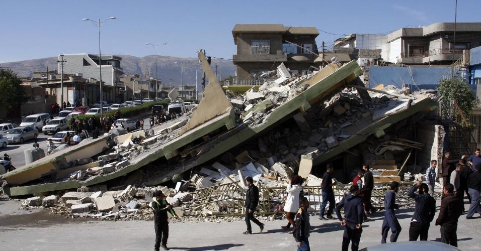 13.nov.2017 - Moradores passam por prédio que desabou devido ao terremoto na cidade de Darbandikhan, no Iraque