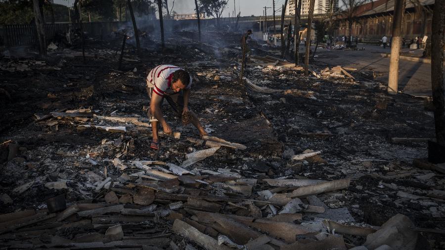 Homem tenta resgatar pertences em meio a escombros de incêndio na favela do Cimento, na zona leste de São Paulo - Danilo Verpa/Folhapress