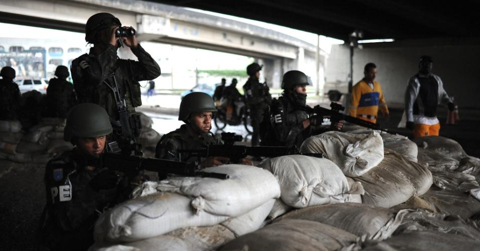 19.jun.2015 - Em barricada, militares das Forças Armadas observam movimentação na comunidade Vila dos Pinheiros, no complexo da Maré, zona norte do Rio de Janeiro. A Força de Pacificação vai deixar as favelas no dia 30 de junho, após 15 meses de ocupação