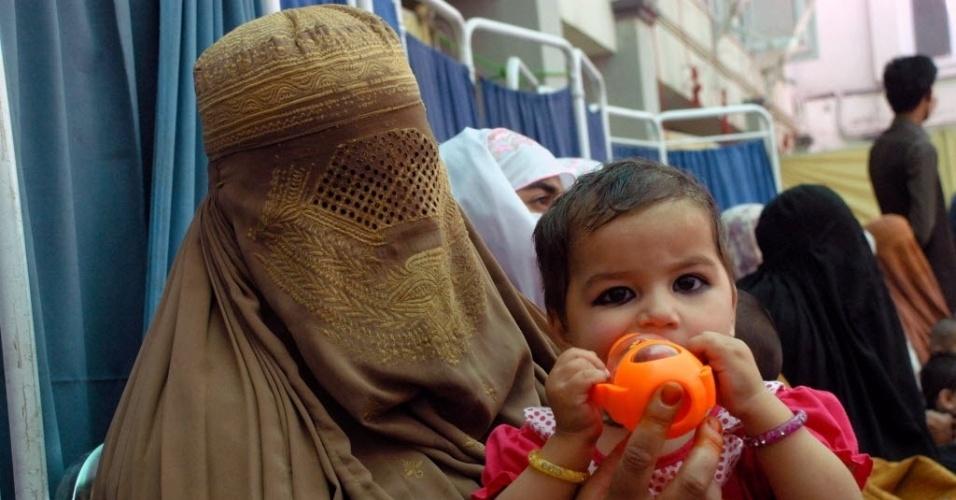 7.mai.2016 - Mulher vestindo burka alimenta criança em clínica médica na véspera das celebrações do Dia das Mães no Paquistão