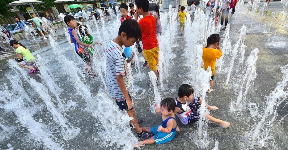 4.ago.2016 - Crianças brincam em uma fonte no centro de Seul, na Coreia do Sul. O país emitiu um alerta sobre uma onda de calor que chegou a região. A temperatura deve se manter acima de 35ºC
