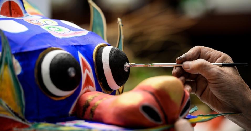 2.set.2016 - O artista Cheng Dishen pinta uma pipa em forma de dragão no museu de Artesanato de Hangzhou, na China. O artesanato local e as peças de patrimônio cultural imaterial são exibidas no local