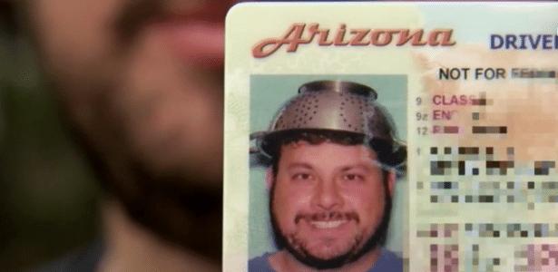Sean Corbett mostra a foto na sua carteira de motorista