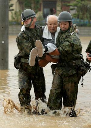 Soldados ajudam morador local a deixar área alagada na cidade de Fukuoka