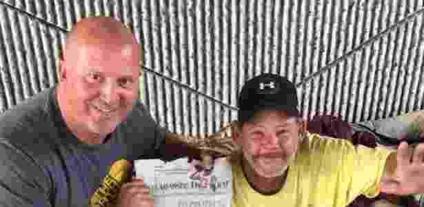 Carlson posa ao lado de Phil, após sua entrevista de emprego, segurando uma reportagem local sobre a história - TALLAHASSEE POLICE DEPARTMENT/FACEBOOK