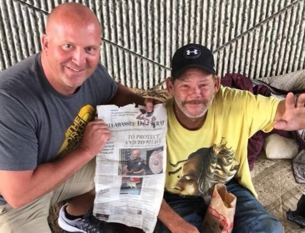 Carlson posa ao lado de Phil, após sua entrevista de emprego, segurando uma reportagem local sobre a história