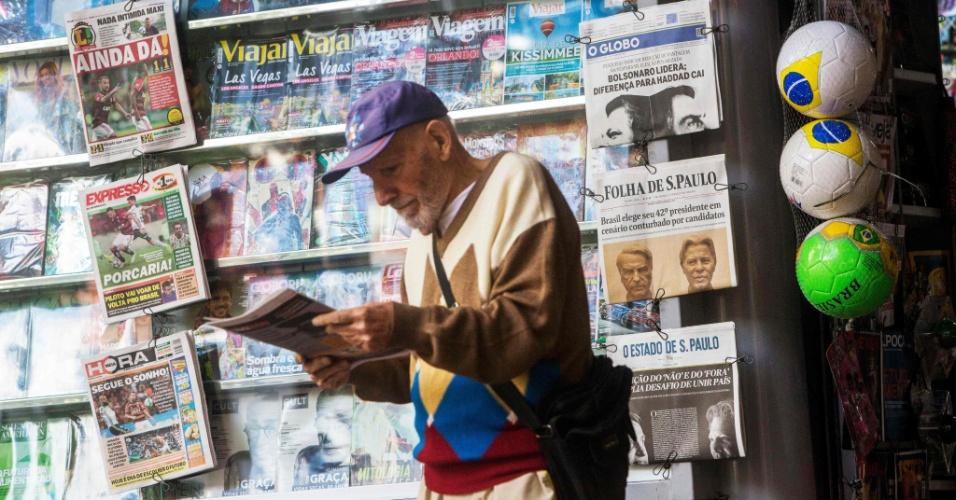 28.out.2018 - Homem lê a primeira página de um jornal sobre a eleição nacional do segundo turno, em Botafogo, momentos antes da abertura das seções eleitorais no Rio de Janeiro