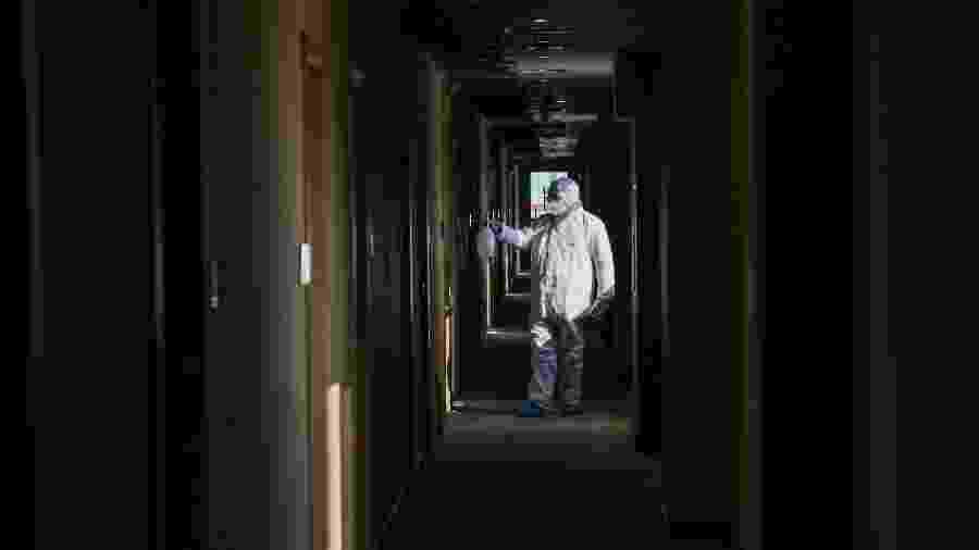 Membro da equipe médica desinfetando um hotel convertido em zona de isolamento na província de Hubei, China - STR/AFP