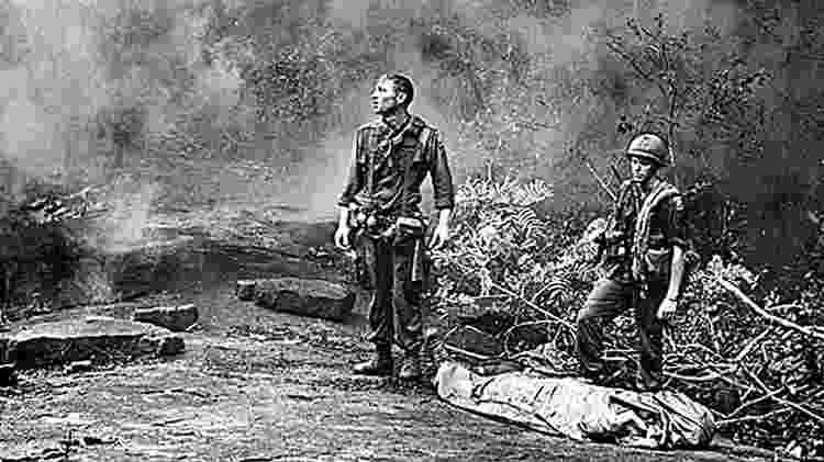 Norte-americanos esperam, ao lado do corpo de um colega morto, o helicóptero que os levaria da selva na Província de Long Khank, em 1966 - AFP/National Archive - AFP/National Archive