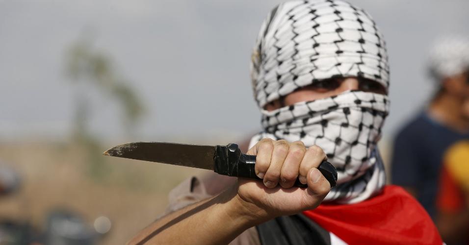 9.out.2015 - Palestino mascarado exibe faca durante protesto próximo à fronteira da faixa de Gaza com Israel