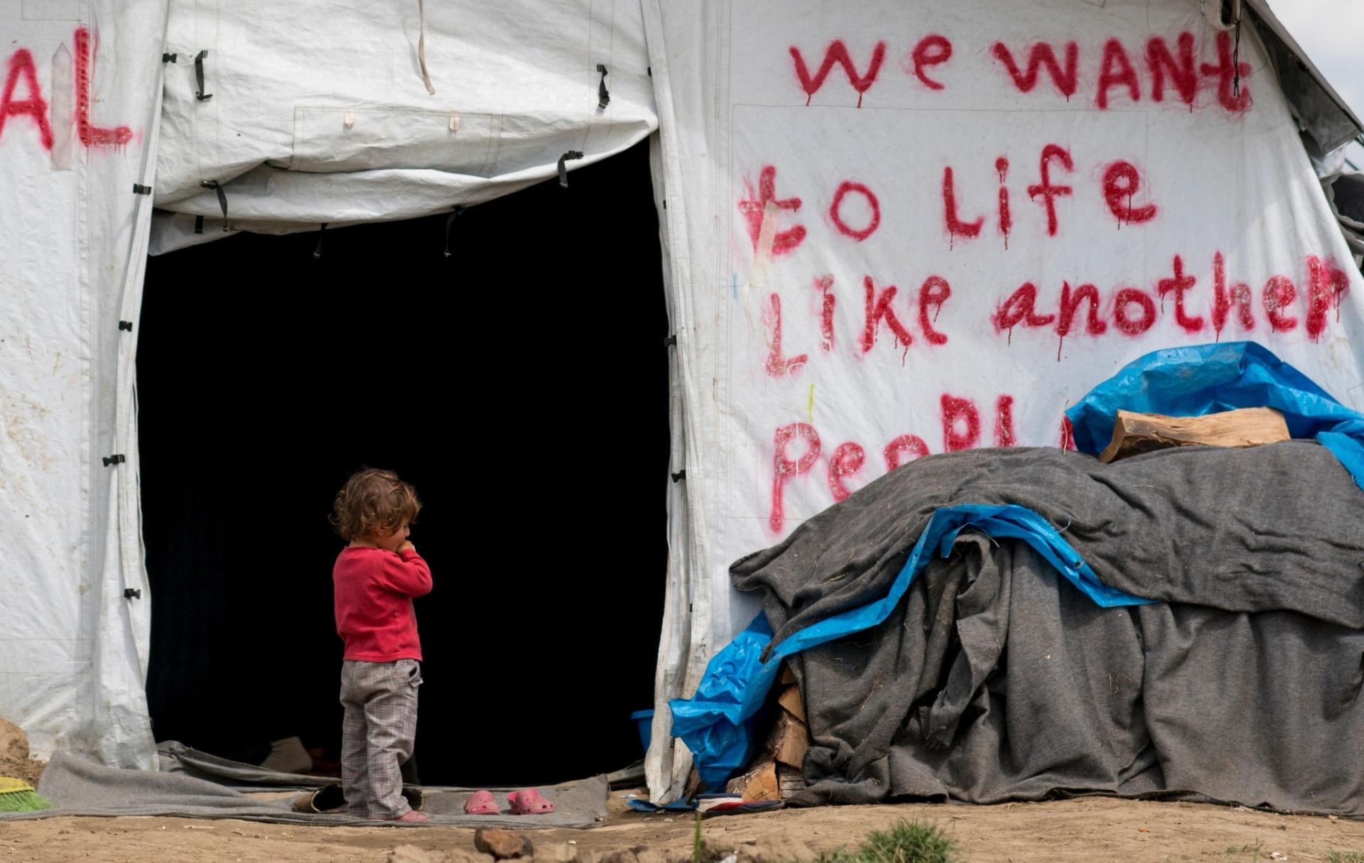 24.abr.2016 - Garota refugiada fica na frente de uma tenda onde se pode ler