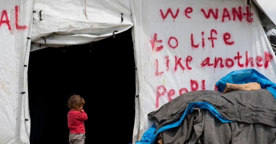 """24.abr.2016 - Garota refugiada fica na frente de uma tenda onde se pode ler """"Nós queremos viver como as outras pessoas"""", em um acampamento improvisado no vilarejo de Idomeni, na fronteira dentre a Grécia e a Macedônia"""
