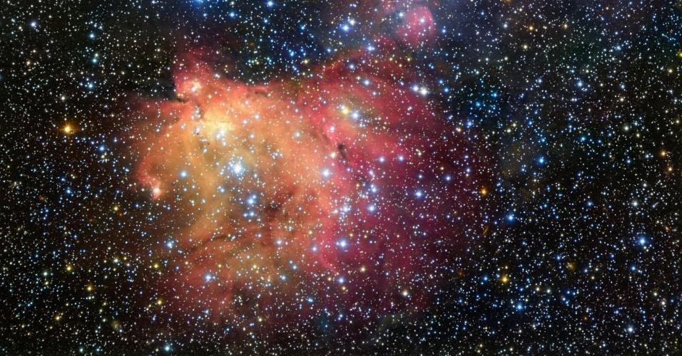 """18.mai.2016 - BRILHANTE E AZUIS, ESTRELAS SE ENFEITAM COM NEBULOSA: Um telescópio do ESO (Observatório Europeu do Sul) registra o forte brilho de um grupo de jovens estrelas azuis e brancas, chamado de LH 72. Esta luz energiza o gás que restou da recente formação estelar, que aconteceu há """"apenas"""" alguns milhões de anos. O resultado dessa atividade é a colorida nebulosa, chamada LHA 120-N55, que está localizada na Grande Nuvem de Magalhães, uma galáxia satélite da Via Láctea a cerca de 163 mil anos-luz de distância. Na imagem, as estrelas parecem se """"enfeitar? com o manto de gás brilhante da nebulosa. Os astrônomos estudam este fenômeno para aprender mais sobre as condições existentes nos locais onde novas estrelas se desenvolvem"""