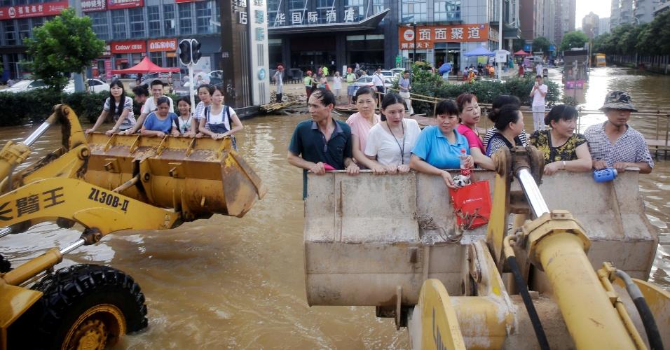 8.jul.2016 - Chineses tomam retroescavadeiras para ir ao trabalho durante inundação em Wuhan, na província de Hubei, na China