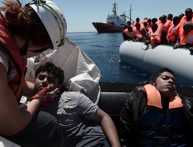 Resgatista atende garoto dentre um grupo de migrantes resgatado no Mar Mediterrâneo