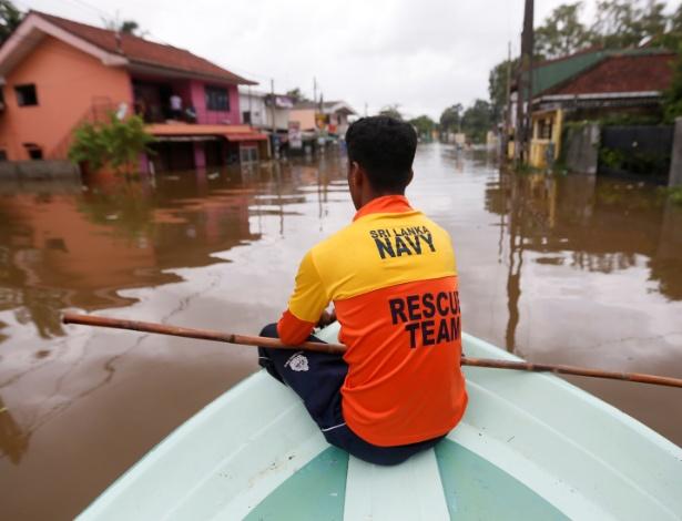Membro das equipes de resgate procura por vítimas em vilarejo da cidade de Kalutara