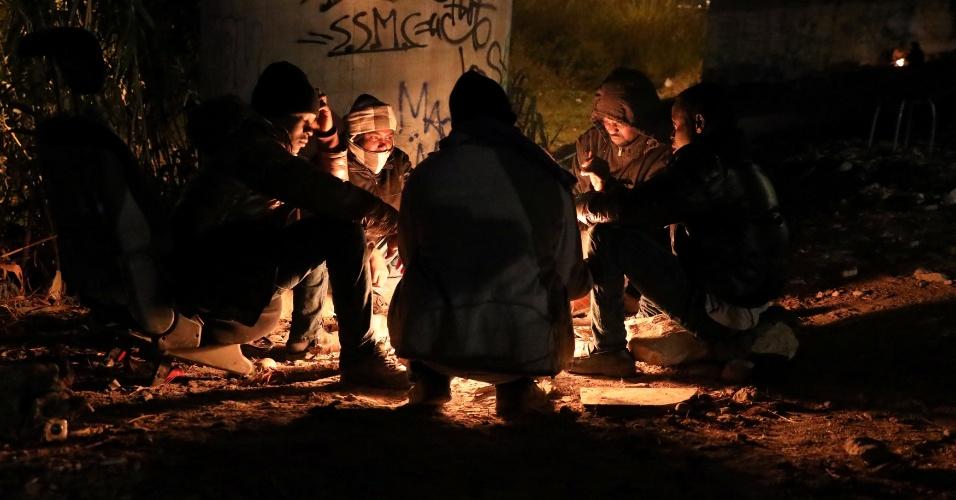 Imigrantes se aquecem numa fogueira, sob um viaduto, antes de tentarem cruzar os Alpes