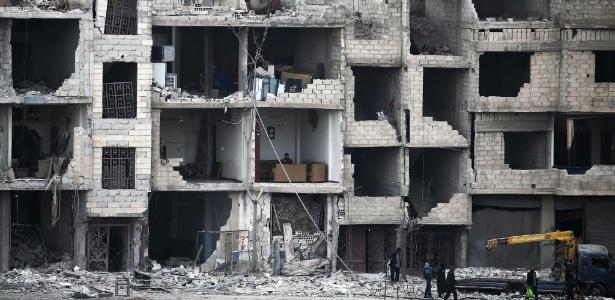 Moradores passam por prédios destruídos em Arbin, em Ghouta Oriental, na Síria