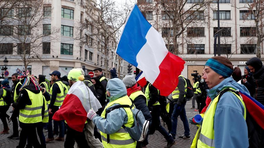 """""""Coletes amarelos"""" protestam na Champs Elysées, em Paris. As manifestações ainda estão servindo de oportunidade amorosa para alguns franceses. - Benoit Tessier/Reuters"""