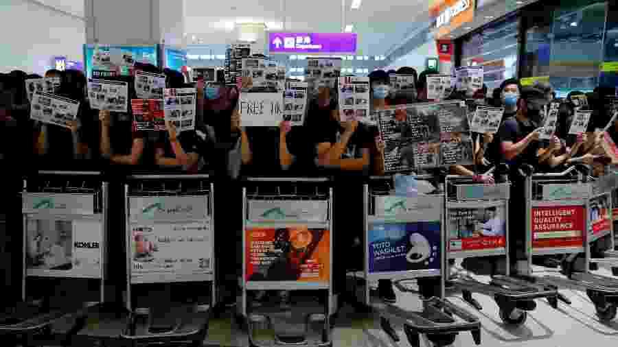 Manifestantes anti lei de extradição de Hong Kong utilizam carrinhos para impedir passageiros de embarcarem em voos - Tyrone Siu/Reuters