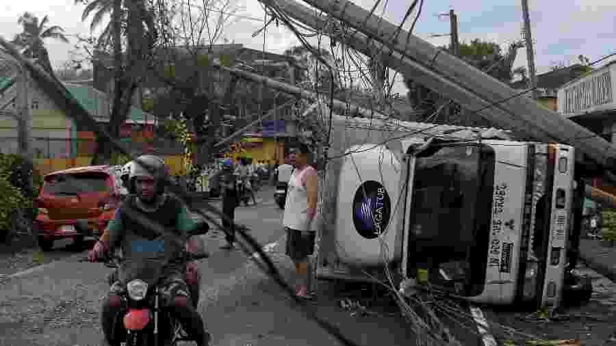 3.dez.2019 - Tufão Kammuri derrubou postes e virou carros na cidade de Camalig, nas Filipinas - Reuters