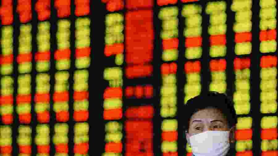 Investidora usa máscara de prevenção contra vírus enquanto monitora ações em Xangai, China - Claro Cortes