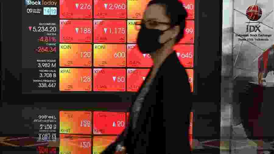 Mulher vestindo máscara passa em frente a tela mostrando dados da Bolsa da Indonésia, em Jacarta, em dia de caos nos mercados mundiais - Adek Berry/AFP