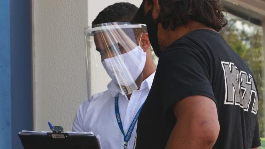 Funcionário da Caixa usa equipamento de proteção para fazer atendimento a cliente durante a pandemia do novo coronavírus - Divulgação/Fenae