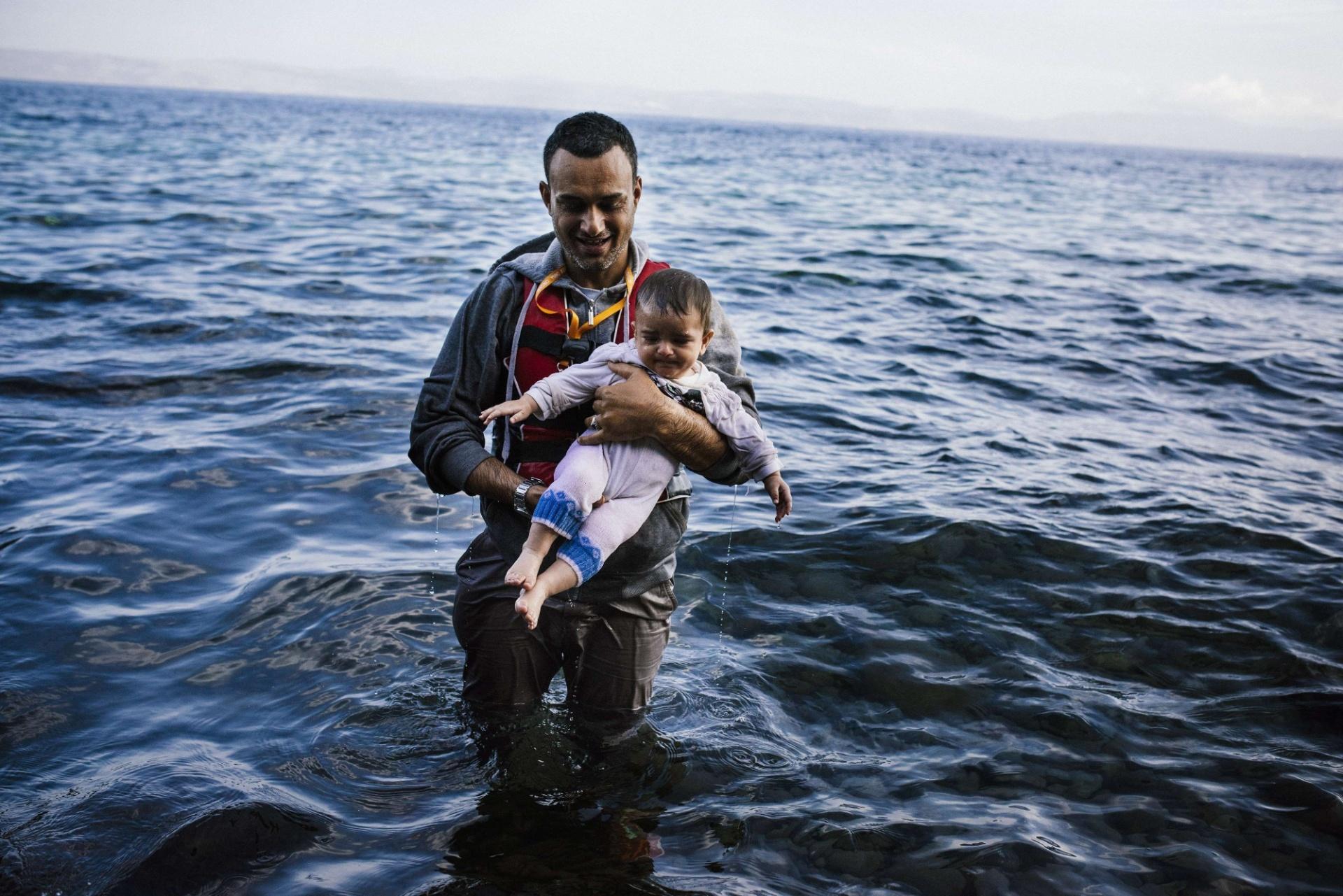 12.out.2015 - Um homem leva seu filho logo após chegar, com outros refugiados e migrantes, à ilha grega de Lesbos, depois de atravessar o mar Egeu a partir da Turquia. A Grécia foi atingida por uma nova onda de imigrantes após a ONU aprovar em 9 de outubro uma operação militar europeia para combater o tráfico de pessoas na região do Mediterrâneo