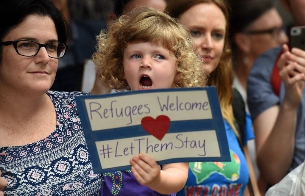 """5.fev.2016 - Durante protesto em apoio aos imigrantes em Brisbane, na Austrália, uma menina exibe cartaz com a frase """"Refugiados são bem-vindos #deixemelesficarem"""""""