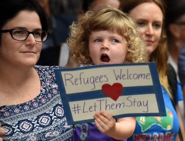 """Durante protesto em apoio aos imigrantes em Brisbane, na Austrália, uma menina exibe cartaz com a frase """"Refugiados são bem-vindos #deixemelesficarem"""""""