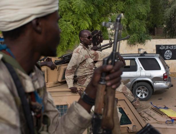 18.mar.2016 - Soldados do Chade passam por bandeira do Boko Haram, uma de muitas presentes na cidade de Damasak, no norte da Nigéria - Tyler Hicks/The New York Times